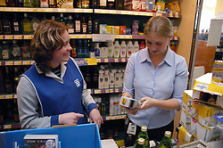 Shop assistants using bar code machine at checkout in supermarket,