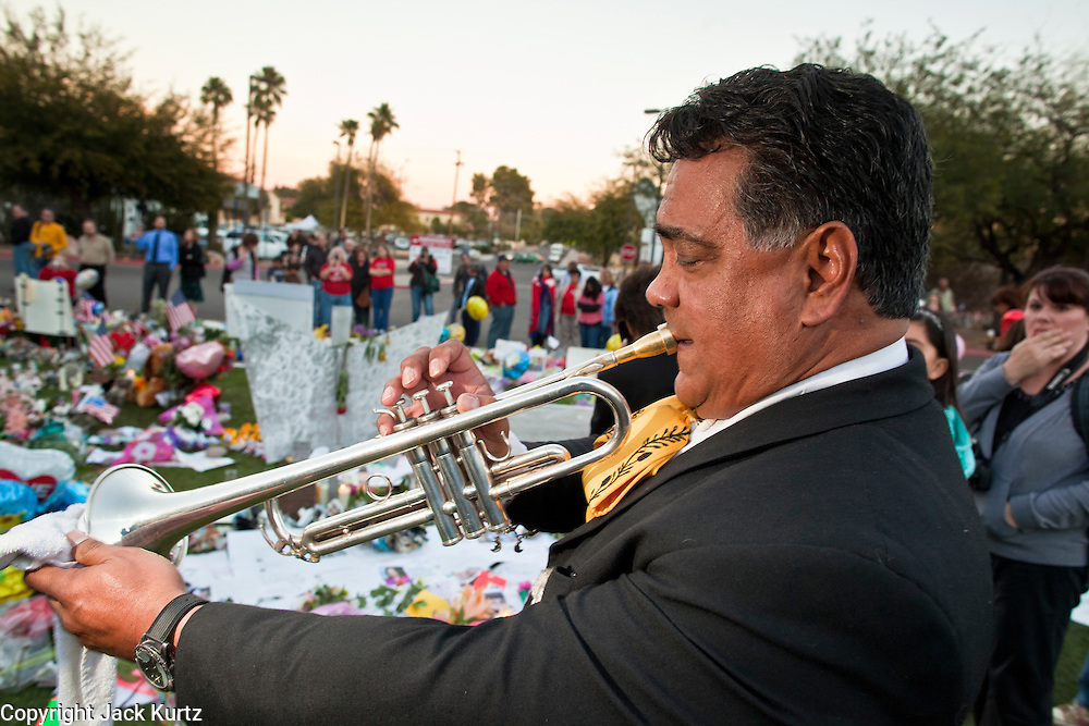 """15 JANUARY 2011 - TUCSON, AZ: RUBEN MORENO, from the Mariachi group Luz de Luna (Light of the Moon) performs at the memorial on the lawn in front of the University Medical Center in Tucson, AZ, Saturday, January 15. The memorial has been growing since the mass shooting last week. Six people were killed and 14 injured in the shooting spree at a """"Congress on Your Corner"""" event hosted by Congresswoman Gabrielle Giffords at a Safeway grocery store in north Tucson on January 8. Congresswoman Giffords, the intended target of the attack, was shot in the head and seriously injured in the attack. She is hospitalized at UMC. Hospital staff have told the musicians that their music can be heard in Giffords' room. The alleged gunman, Jared Lee Loughner, was wrestled to the ground by bystanders when he stopped shooting to reload the Glock 19 semi-automatic pistol. Loughner is currently in federal custody at a medium security prison near Phoenix.  Photo by Jack Kurtz"""