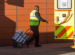 © Licensed to London News Pictures.25/01/2021, London,UK. A hospital worker is seen carrying tanks of liquid oxygen at the Royal London Hospital in east London as the third national lockdown continues and hospitals are struggling to cope with the number of admissions. Photo credit: Marcin Nowak/LNP