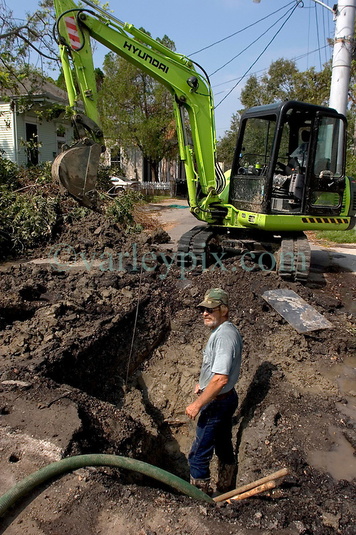 30 Sept, 2005. New Orleans, Louisiana.<br /> Private contractor Kenny Meyer of Hydro Air in Chalmette fixes a leaking water main in Uptown New Orleans as businesses and locals return to the city. <br /> Photo; ©Charlie Varley/varleypix.com