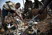 Young men pull apart the contents of computer monitors and other electronics to recover copper and other metals that can be sold for money near the Agbogboloshie market in Accra, Ghana on Thursday August 21, 2008.