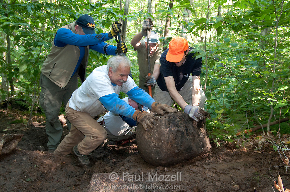 Members of Trailwrights, a club of volunteers who repair and build hiking trails around New England, build a rock step on The Pemmigiwasett Trail in Franconia Notch, NH. Ray Jackson in blue and white, is the groups leader.