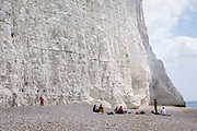 Tourists picnicking on Cuckmere Haven beach, very close to the cliff edge of Seven Sisters Cliffs on the 25th of August 2021 near Seaford, East Sussex, United Kingdom. The Seven Sisters are a series of chalk cliffs by the English Channel. They form part of the South Downs in East Sussex, between the towns of Seaford and Eastbourne in southern England. Cliff falls are common along these cliffs as they are formed from chalk.