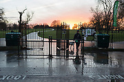 A dog walker leads her pet through the gates of Brockwell Park, a public space in Lambeth, on 11th December 2017, in London England.
