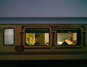 Passengers relax in their bed on the Palace on Wheels, a vintage luxury train crossing Rajahstan province.