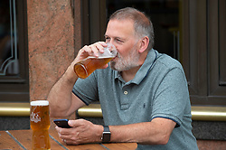 ©Licensed to London News Pictures 15/07/2020     <br /> Petts Wood, UK. This man enjoying 15 percent off his beer outside the Wetherspoon pub in Petts Wood, South East London. Chancellor Rishi Sunak has cut VAT on beer and food for six months to help pubs and restaurants get back on their feet after coronavirus. Photo credit: Grant Falvey/LNP
