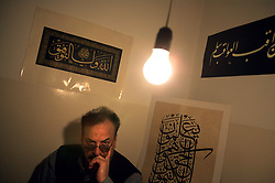 Abbas Shaker Jawdeh, also known as Abbas Al-Baghdadi, is seen in his studio in Amman, Jordan, Feb. 2, 2004. Jawdeh spent two years writing the Koran with the blood of Saddam Hussein.