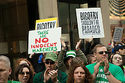 Protestors carry signs condemning the parade committe for not allowing gay, lesbian or transgendered contingents to march.