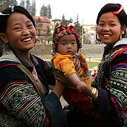 Black Hmong women with their children in Sapa market place, Northern Vietnam. Sapa and the surrounding highlands are close to the Chinese border in Northern Vietnam and are inhabited by highland minorities including Hmong and Dzao groups. Sapa is now a thriving tourist destination for travelers taking the night train from Hanoi. Sapa, Vietnam. 16th March 2012. Photo Tim Clayton