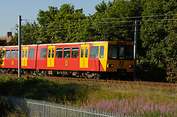 Newcastle Metro: train with red and yellow livery in coastal area of Tynemouth UK