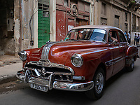 Orange classic car taxi cruising for a fare in Old Havana.