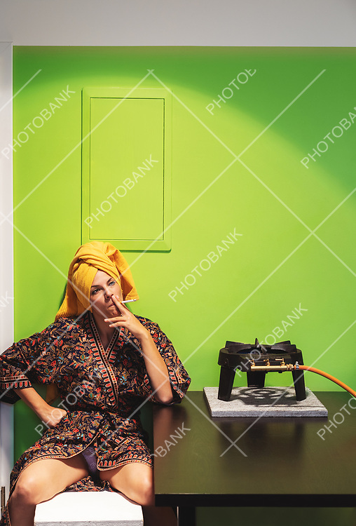 Young sexy and depressed woman in a nightgown approaches the gas stove and lights a cigarette. Green screen