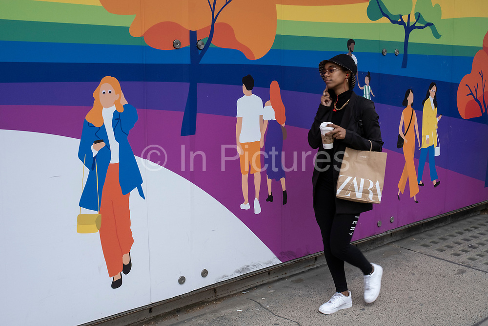People interacting with figures on a hoarding outside a shop being refitted on the Kings Road in the upmarket area of Chelsea on 14th April 2021 in London, United Kingdom. Chelsea is one of the principal areas for mid-range, exclusive or luxury goods in West London. It is known as a district where the rich and wealthy shop, mostly for high end ad well as high street fashion and jewellery.