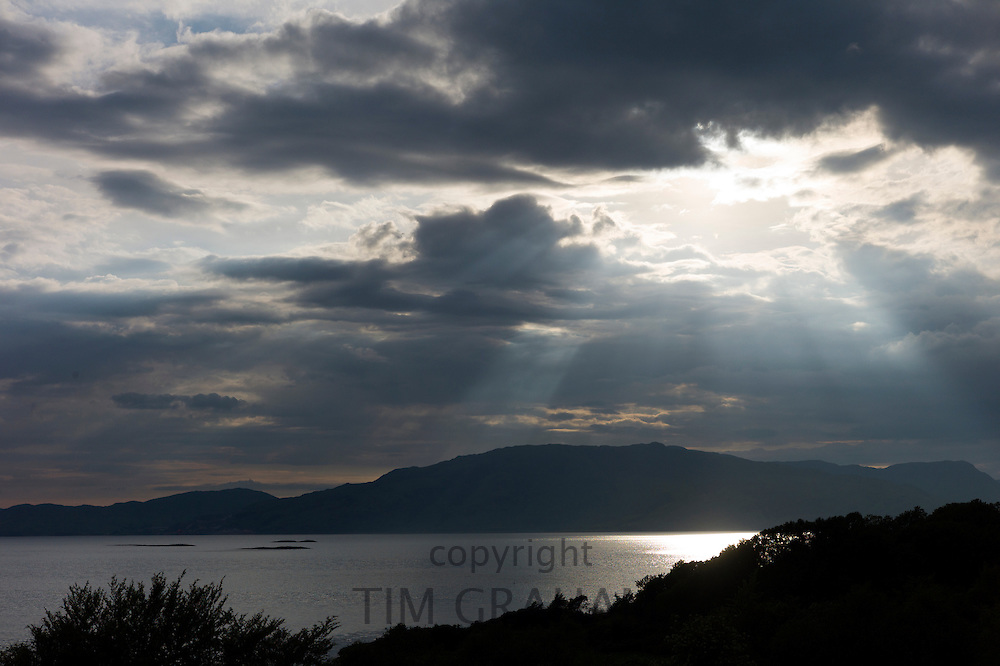 Sun's rays break through grey clouds onto Loch Linnhe in late afternoon early evening near Strontian, Argyll, in the Highlands of Scotland