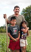 A farmer and his kids tend vegetables at the Adelante Mujeres Farm in Forest Grove, Oregon.