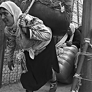MELILLA, SPAIN - APRIL 20, 2010 : Women carrying  goods up to 80 kg. in weight  of smuggling through the border of  El Barrio Chino between Spain and Morocco on April 20 , 2010 in Melilla. Spain. Every day at the pedestrian border of El Barrio Chino hundreds of people are involved in transporting smuggled goods from Melilla a Spanish enclave on the North African coast to Morocco.For each package introduced in Morocco receive between 3 an 5 euros depending on size,with a little luck achieved make three trips a day.It is estimated that from Monday to Thursday on foot enter Melilla 8.000 porters, mostly women, to return to Morocco with huge sacks of goods from the warehouse border area of Beni Enzar in Melilla .( Photo by Jordi Cami )
