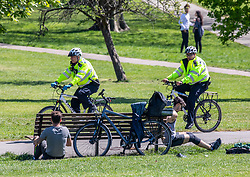 © Licensed to London News Pictures. 19/04/2020. London, UK. Two Police cyclists patrol Primrose Hill enforcing lockdown rules on social distancing as members of the public exercise as Ministers urge councils to keep parks open to the public during lockdown. Photo credit: Alex Lentati/LNP