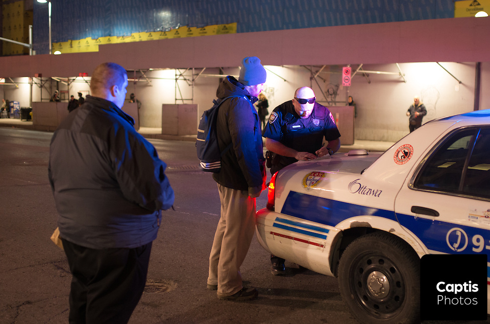 """Police interview witnesses after a man was assaulted on Rideau St. between Sussex Dr. and Dalhousie St. A witness said the victim made """"racist comments"""" being assaulted by multiple attackers.<br /> Police say the man was unconscious when being transported to hospital and is in non-life threatening condition. March 31, 2015.<br /> Captis Photos / Brendan Montgomery"""