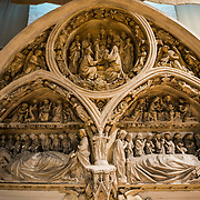 An ornate gothic stone  portal on display in a large hall at the Old St. John's Hospital in Brudges, Belgium. The unusual iconography combines two popular themese from gothic portals that can be found throughout the north of France: portal of the Virgin Mary and the Last Judgment. Old St. John's Hospital is one of Europe's oldest surviving hospital buildings that dates to the 11th century. It originally treated sick pilgrims and travelers. A monastery and convent was later added. It is now a museum.