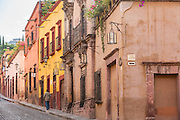 A man walks past the Spanish colonial adobe buildings along Jesus Street in the historic center of San Miguel de Allende, Mexico.