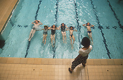School swimming lesson with teacher and pupils,