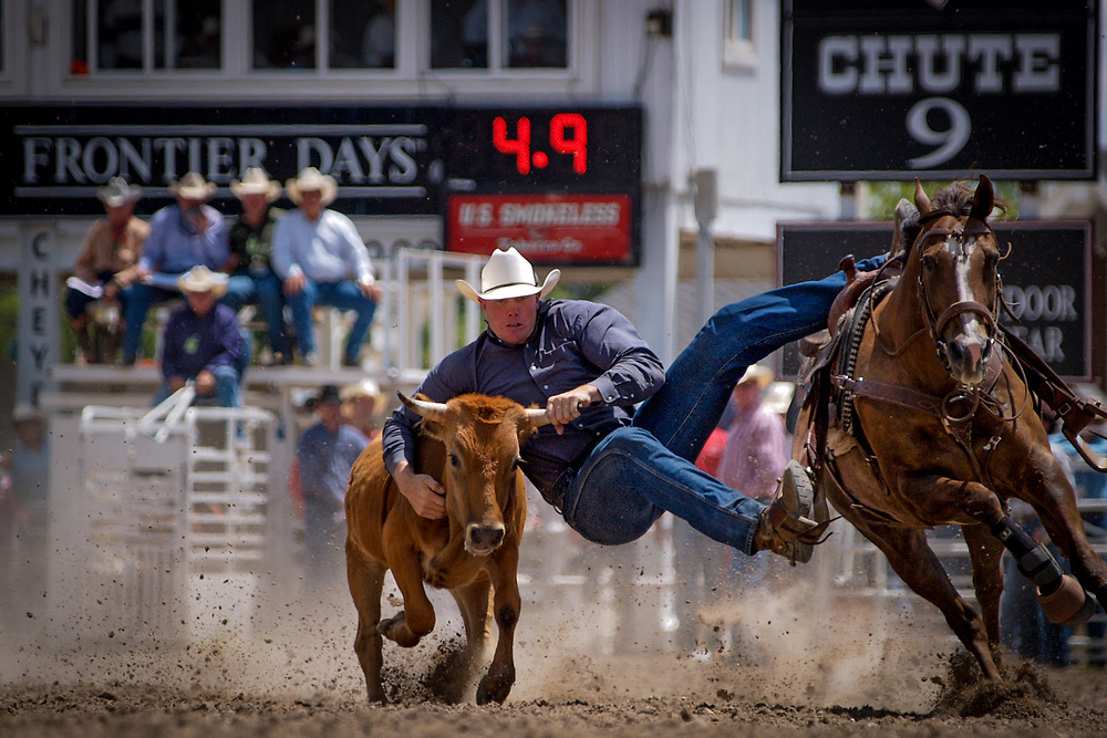 JAKE RINEHART of Highmore, South Dakota competes in the Steer Wrestling event at Cheyenne Frontier Days.