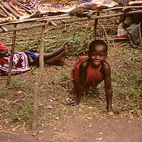 Africa, Kenya, Maasai Mara. A young Maasai boy sneaking out at Olanana in the Maasai Mara.
