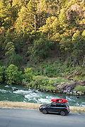 SUV with whitewater kayak parked next to the Trinity River, Shasta-Trinity National Forest, California