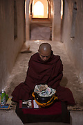 A monk meditates in a temple while people donate money, Bagan, Burma<br /> Note: These images are not distributed or sold in Portugal