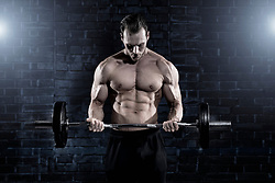 Muscular man doing barbell biceps curls exercise