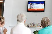 Een groep ouderen kijkt in het zwembad in De Meern naar een fictieve melding van het Amber Alert. Via beeldschermen in winkelcentra, buurthuizen etc wordt melding gemaakt van het Amber Alert. De dienst is opgezet om de politie te helpen bij het opsporen van vermiste kinderen en wordt alleen in de hoognodige gevallen gebruikt..FICTIEVE MELDING<br /> <br /> An Amber Alert on a screen in a cantine. Fictive alarm!
