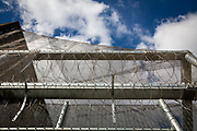 Anti-drone netting has be attached to the top of the large metal security fence with additional razor wire protects a Prison Wing of HMP Pentonville, London, UK.  The brick wing wall can be seen in the background with multiple windows of individual cells. Pentonville is a local prison and holds Category B and C males and A Wing is for this who are on remand and convicted. The prison was built in 1816 as a modern prison and was uniquely designed for rehabilitation. (Photo by Andy Aitchison)