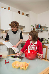 Two senior woman comparing recipe on digital tablet and cookery book , Munich, Bavaria, Germany