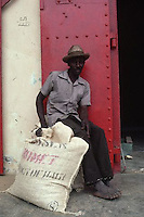 December 1985, Haiti --- Man Sitting With a Sack of Coffee Beans --- Image by © Owen Franken/CORBIS