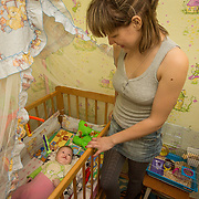 """CAPTION: Lying in her cot, baby Valentina smiles up at her doting mother. """"I wanted our baby to have her own room"""", says her father, """"and to grow up like a princess"""". Arranging corrective surgery for their little girl was this young couple's highest priority after she was born with a cleft lip. LOCATION: Volzhskiy, Volgograd Oblast, Russia. INDIVIDUAL(S) PHOTOGRAPHED: Valentina Panteleeyeva (below) and Nina Panteleeyeva (right)."""