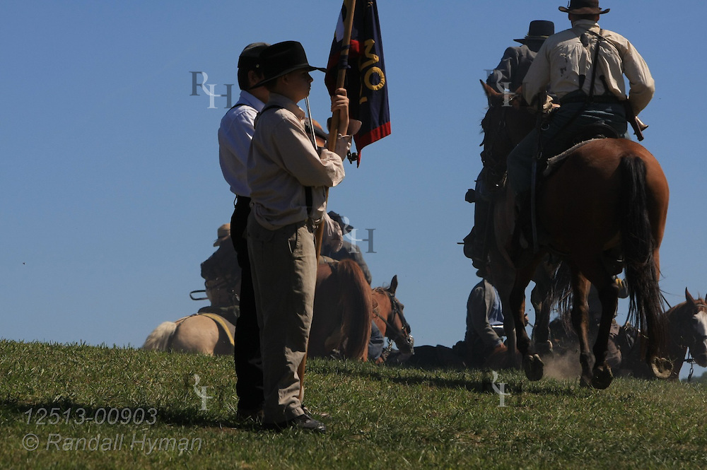 Boy holds flag while partner fiddles a tune as Confederates prepare for Civil War battle reenactment at Hermann, Missouri.