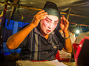"""06 DECEMBER 2015 - BANGKOK, THAILAND: A Chinese opera performer puts on his costume before going on stage at the Ruby Goddess Shrine in the Dusit district of Bangkok. Chinese opera was once very popular in Thailand, where it is called """"Ngiew."""" It is usually performed in the Teochew language. Millions of Chinese emigrated to Thailand (then Siam) in the 18th and 19th centuries and brought their culture with them. Recently the popularity of ngiew has faded as people turn to performances of opera on DVD or movies. There are about 30 Chinese opera troupes left in Bangkok and its environs. They are especially busy during Chinese New Year and Chinese holidays when they travel from Chinese temple to Chinese temple performing on stages they put up in streets near the temple, sometimes sleeping on hammocks they sling under their stage.     PHOTO BY JACK KURTZ"""