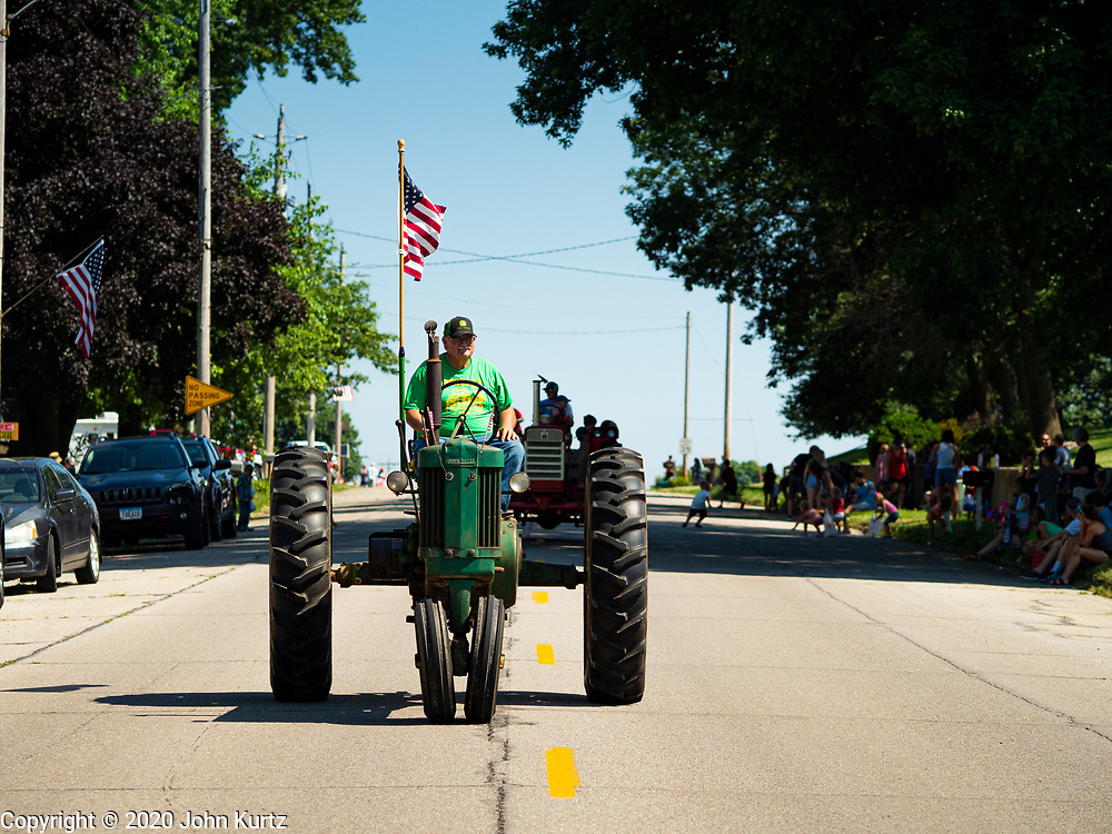 04 JULY 2020 - RUNNELLS, IOWA: People on tractors during the 4th of July tractor parade in Runnells, a small community about 25 miles from Des Moines. Most of the Independence Day parades in central Iowa were cancelled because of the COVID-19 (Coronavirus) pandemic. People in Runnells made the decision to go ahead with their parade, the first 4th of July parade in the town in recent memory. Most of the people in the parade were farmers, who drove their tractors through the town.    PHOTO BY JACK KURTZ