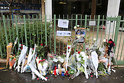 """Flowers, pens, press cards and candles adorn memorial sites on the Richard Lenoir street near to the Charlie Hebdo Offices, in central Paris.<br /><br />French journalists today make a vigil in central Paris next to the Offices of Charlie Hebdo, marking one minute silence at midday, to mourn the death of their colleages. Ten staff including journalists, cartoonists and editors at Charlie Hebdo were killed the day before, when armed gunmen attacked the offices of Charlie Hebdo, killing twelve people including two policemen; four more are in critical condition. It is the deadliest terror attack in France for over fifty years. Charlie Hebdo is a satirical publication well known for its political cartoons. The newspaper had been threatened for making satirical images of the prophet Muhammad.<br /><br />As a solidarity action with the deaths at Charlie Hebdo many placards read """"Je suis Charlie"""" translating as """"I am Charlie (Hebdo)"""". Demonstrators hold aloft pens, brushes and crayons, in solidarity for their dead colleagues, symbolizing the profession of journalists and cartoonists who were killed. Many pens and candles have been placed in shrines throughout the city."""