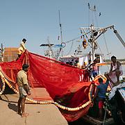 Men hauling a fishing net into an industrial fishing boat.