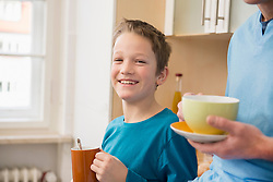 Smiling boy with father in kitchen