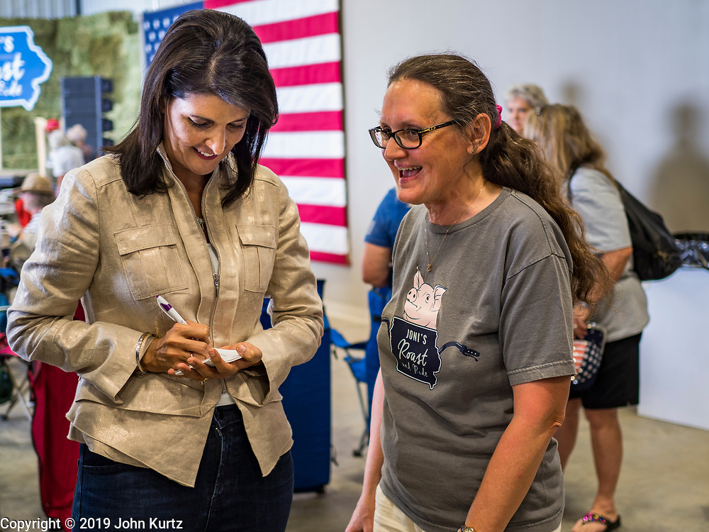 "15 JUNE 2019 - BOONE, IOWA: Former UN Ambassador NIKKI HALEY signs an autograph at ""Joni's Roast and Ride,"" an annual fund raiser held by US Senator Joni Ernst (R-IA). Ernst, Iowa's junior US Senator, kicked off her re-election campaign during the ""Roast and Ride"", an annual fund raiser and campaign event has she held since originally being elected to the US Senate in 2014. PHOTO BY JACK KURTZ"