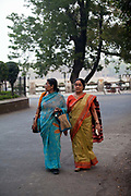 Two women walk arm in arm through Chandannagar, Chandannagar, India