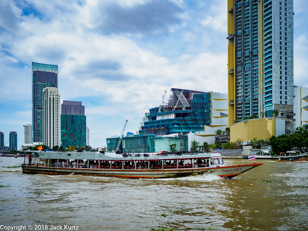 17 SEPTEMBER 2018 - BANGKOK, THAILAND: A Chao Phraya Express Boat goes past the ICONSIAM development on the Chao Phraya River. ICONSIAM is a mixed-use development on the Thonburi side of the Chao Phraya River. It is expected to open in 2018 and will include two large malls, with more than 520,000 square meters of retail space, an amusement park, two residential towers and a riverside park. It is the first large scale high end development on the Thonburi side of the river and will feature the first Apple Store in Thailand and the first Takashimaya department store in Thailand.   PHOTO BY JACK KURTZ