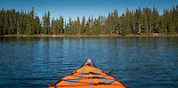 an inflatable kayak is centered in symmetrical image on Forlorn Lake, Gifford Pinchot National Forest, WA  panorama