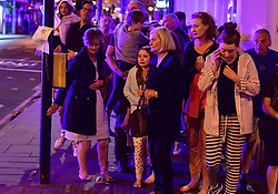 """People walking down Borough High Street as police are dealing with a """"major incident"""" at London Bridge."""