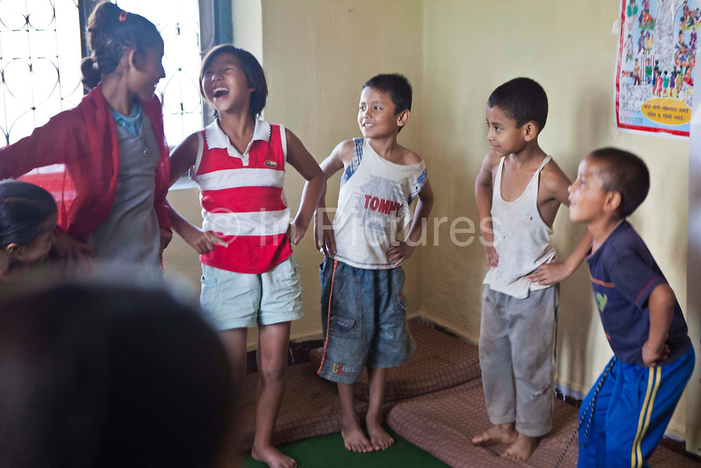 Nepalese children stand and laugh during a play session in a classroom in the Voice for Children rehabilitation center in Kathmandu, Nepal.  The not-for-profit organisation supports street children and those who are at risk of sexual abuse through educational and vocational training opportunities, health services and psychosocial counseling.  These young children have recently been found by the charity and attend the children's drop-in centre where they play games and activities.