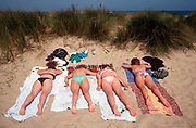 Four young women sunbathe in their bikinis in coastal dunes, on 25th May 1992, in Great Yarmouth, Suffolk, England.
