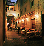 Tourists walking past Restaurant at nigh in Siena, Tuscany, Italy