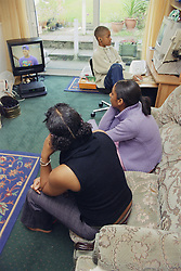Teenage sisters and brother sitting in living room watching television and playing on computer,